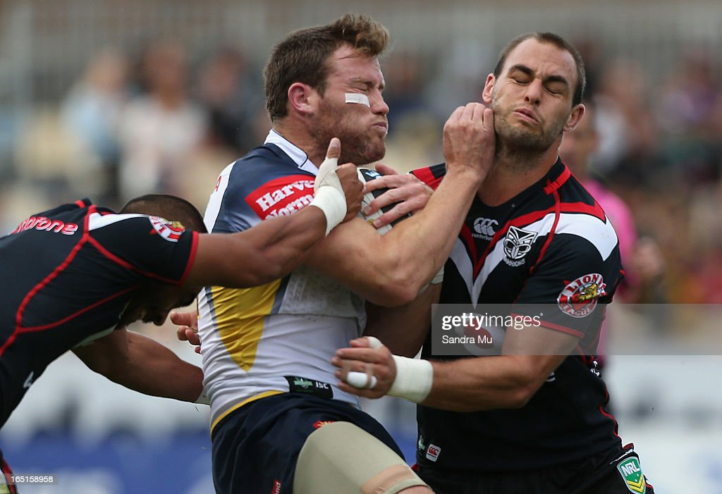 Gavin Cooper of the Cowboys fends off Simon Mannering of the Warriors (R) during the round four NRL match between the New Zealand Warriors and the North Queensland Cowboys at Mt Smart Stadium on April 1, 2013 in Auckland, New Zealand.
