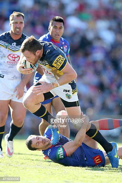 Gavin Cooper of the Cowboys is tackled by Jarrod Mullen of the Knights during the round eight NRL match between the Newcastle Knights and the North...