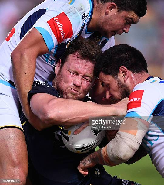 Gavin Cooper of the Cowboys is tackled by Nathan Peats and Ashley Taylor of the Titans during the round 26 NRL match between the North Queensland...