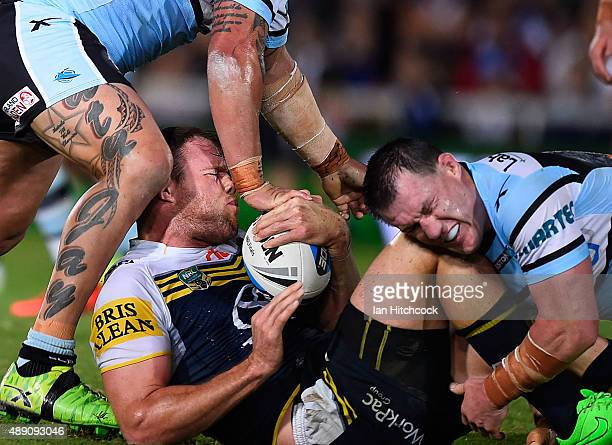 Gavin Cooper of the Cowboys is tackled by Paul Gallen and Andrew Fifita of the Sharks during the Second NRL Semi Final match between the North...
