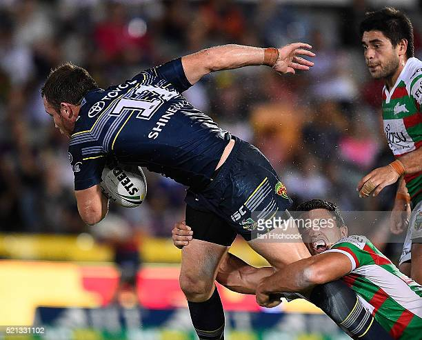 Gavin Cooper of the Cowboys is tackled by Sam Burgess of the Rabbitohs during the round seven NRL match between the North Queensland Cowboys and the...