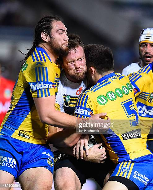Gavin Cooper of the Cowboys is tackled by Tepai Moeroa and Ryan Morgan of the Eels during the round 20 NRL match between the North Queensland Cowboys...