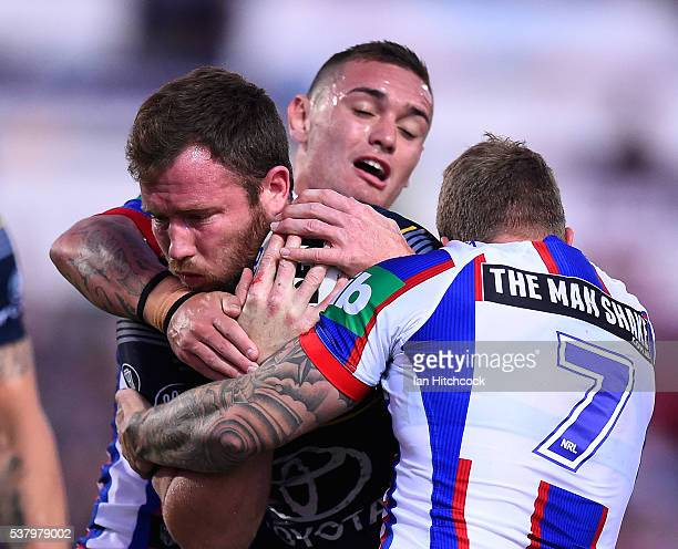Gavin Cooper of the Cowboys is tackled by Trent Hodkinson of the Knights during the round 13 NRL match between the North Queensland Cowboys and the...