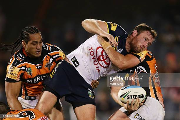 Gavin Cooper of the Cowboys offloads the ball in a tackle during the round 11 NRL match between the Wests Tigers and the North Queensland Cowboys at...