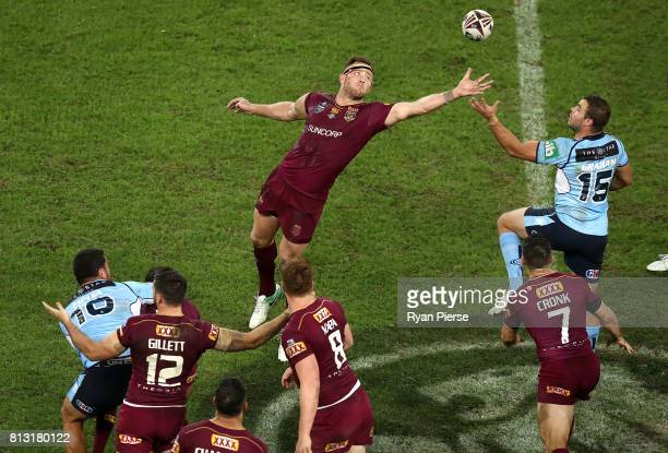Gavin Cooper of the Maroons comeptes for thr ball against Wade Graham of the Blues during game three of the State Of Origin series between the...