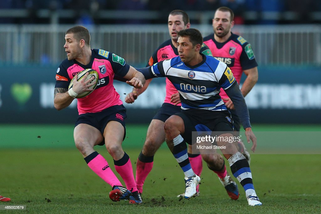 Gavin Evans (L) of Cardiff Blues escapes the challenge from Gavin Henson (R) of Bath during the LV Cup match between Bath and Cardiff Blues at the Recreation Ground on January 25, 2014 in Bath, England.