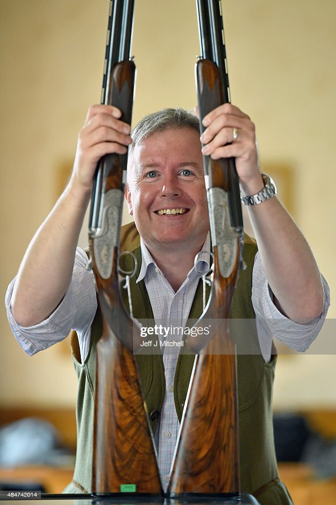 Gavin Gardiner holds a pair of 20bore Holland Holland Sporting model over and under ejector guns at a preview of his annual auction of Modern Vintage...