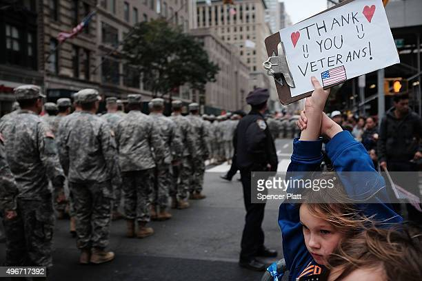 Gavin Kinney holds up a sign thanking veterans at the nation's largest Veterans Day Parade in New York City on November 11 2015 in New York City...