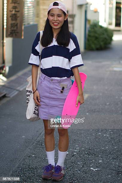 Gawa is seen on Harajuku St wearing a pink ball cap blue and white striped tshirt a lavender skirt by Gogo Sing white sports socks purple New Balance...