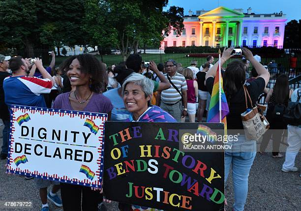 Gay activists hold signs in front of the White House lightened in the rainbow colors in Washington on June 26 2015 The US Supreme Court ruled Friday...