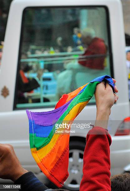 Gay activists wave a rainbow flag at Pope Benedit XVI as they take part in a protest during Pope Benedit XVI's visit to the La Sagrada Familia on...