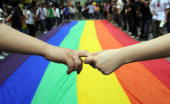 Gay and lesbian activists form a human chain around a rainbow flag during celebrations marking the fourth annual International Day Against Homophobia...