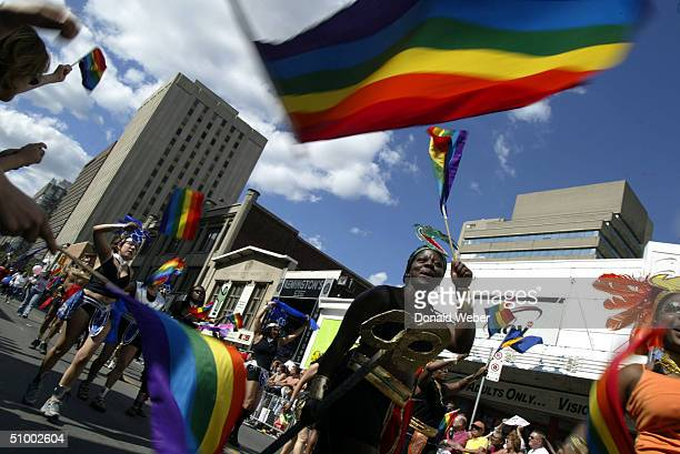 A gay and lesbian parade group marches past spectators during the Pride Parade in support of gay lesbian bisexual transsexual and transgender people...