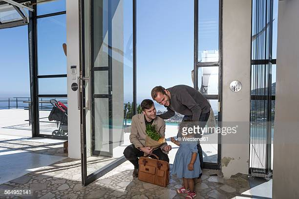 Gay couple and kid at front door with groceries