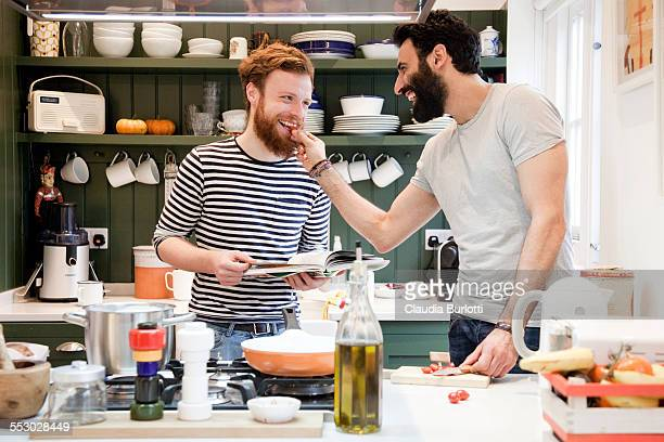 Gay couple cooking together at home