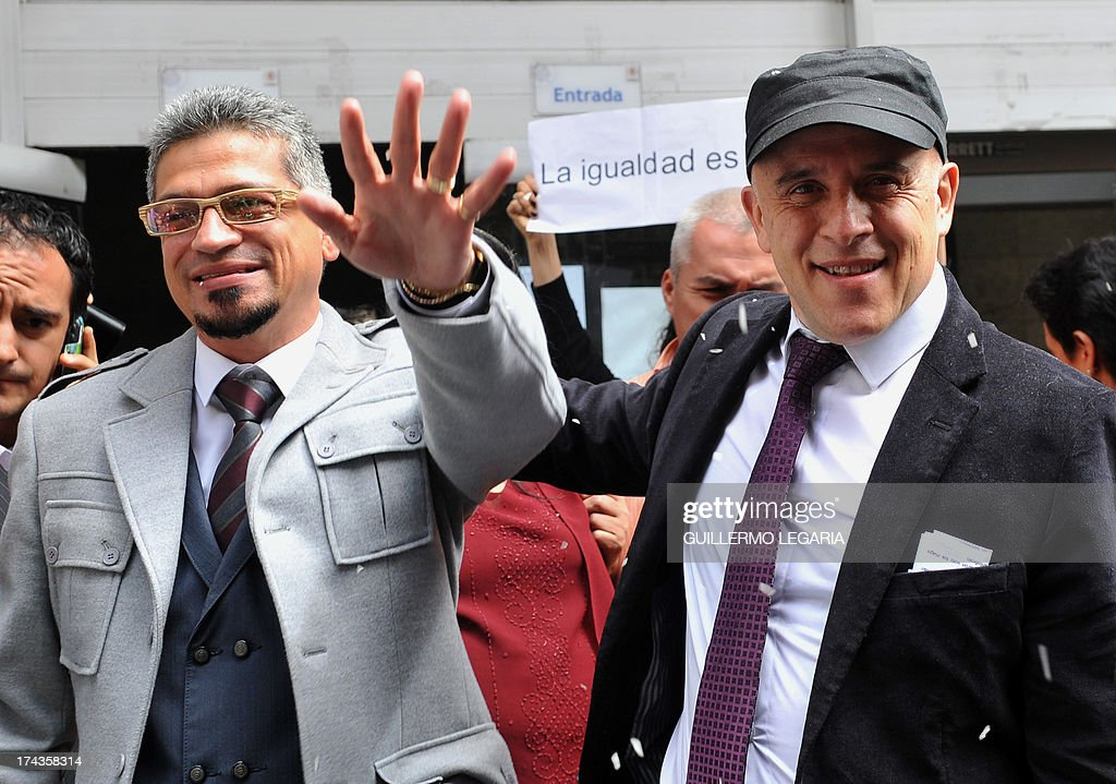 Gay couple Gonzalo Ruiz Giraldo (L) and Carlos Hernando Rivera (R) wave as they leave a local court in Bogota, Colombia, on July 24, 2013, after getting married. Giraldo and Rivera are the first same-sex couple to get married in this country. AFP PHOTO/Guillermo LEGARIA