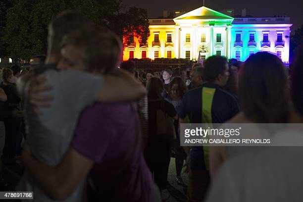 A gay couple hugs in front of the White House lightened in the rainbow colors in Washington on June 26 2015 The US Supreme Court ruled Friday that...