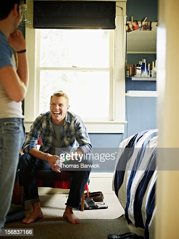 Gay couple in discussion in bedroom laughing : Stock Photo