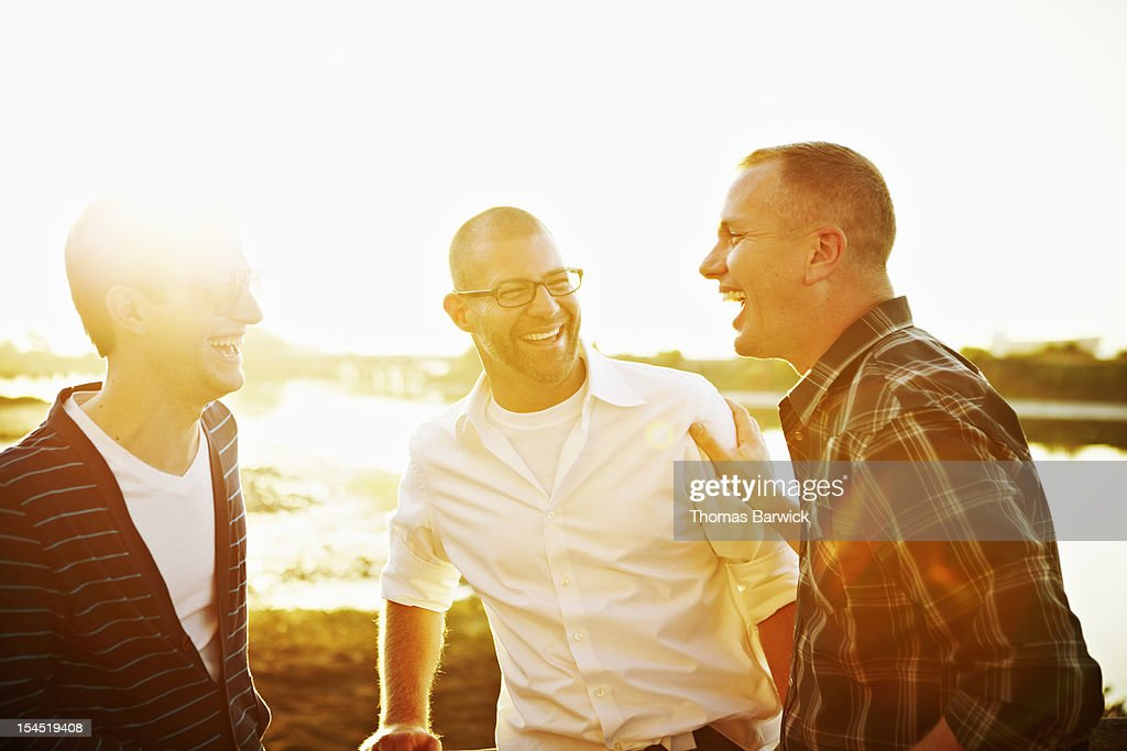 Gay couple in discussion with friend at sunset : Stock Photo