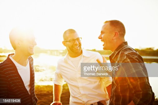 Gay couple in discussion with friend at sunset : Foto de stock