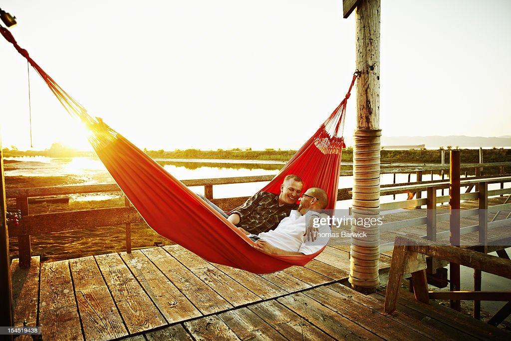 Gay couple in hammock on dock at sunset embracing and laughing