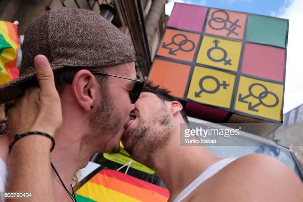 A gay couple kisses during a rally ahead of the Paris Gay Pride Parade or known as Marche des Fiertés LGBT in France at the Place de la Concorde on...