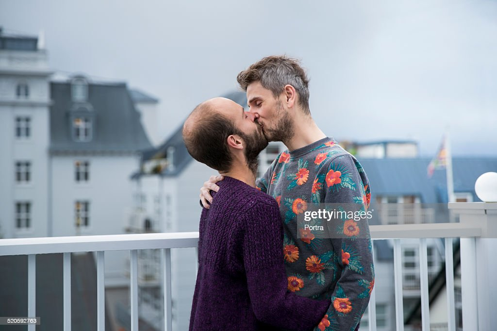 Gay couple kissing railings