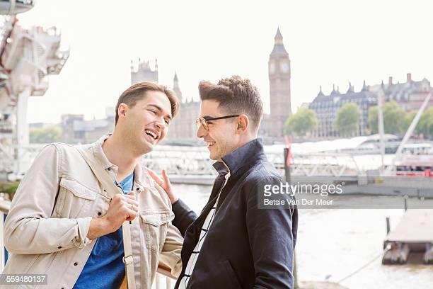 Gay couple laughing near London eye and Big ben