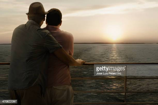 Gay couple looking at sunset from cruise ship balcony
