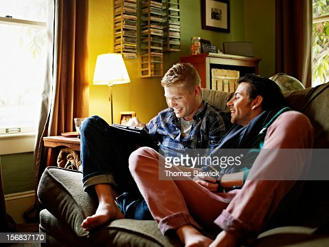 Gay couple on couch looking at digital tablet : Foto stock
