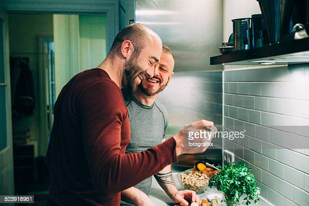 gay couple preparing the meal in the kitchen