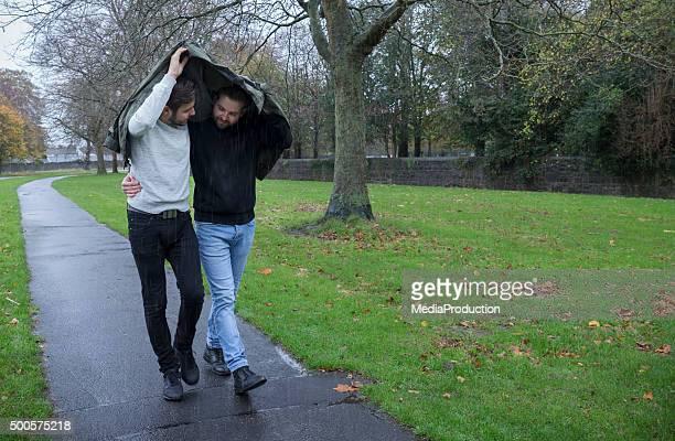 Gay Paar in eine Jacke schützen vor Regen