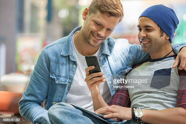 gay couple sharing something on the cellphone.