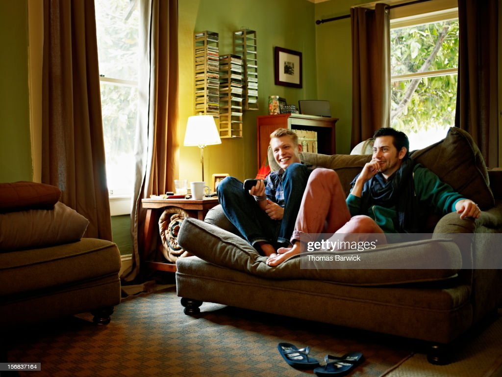Gay couple sitting on couch in home watching TV : Stock Photo