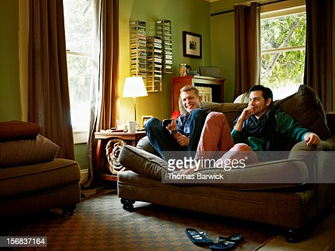 Gay couple sitting on couch in home watching TV : Bildbanksbilder