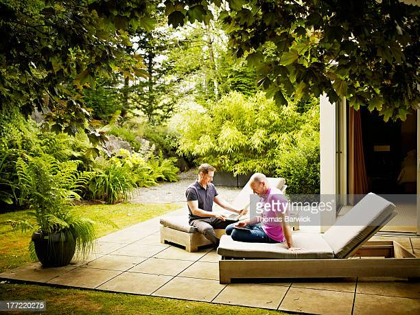 Gay couple sitting on patio of home