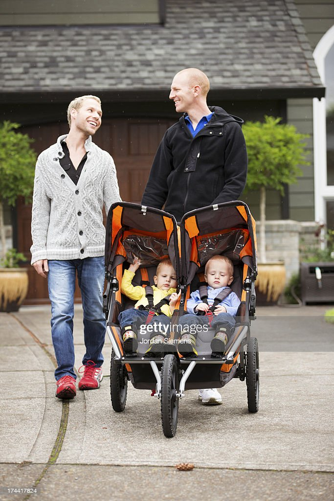 A same sex couple pushing their children in a stroller.