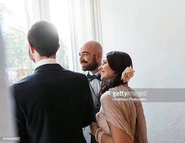 Gay Couple with Bridesmaid Standing by a Window