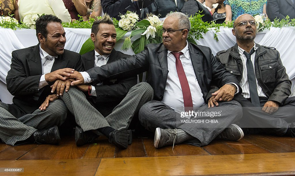 Gay couples celebrate after getting married at the Court of Justice of the State of Rio de Janeiro, on December 8, 2013. 130 gay couples are getting married in the first massive wedding ceremony since the first gay marriage in Rio de Janeiro in 2011.