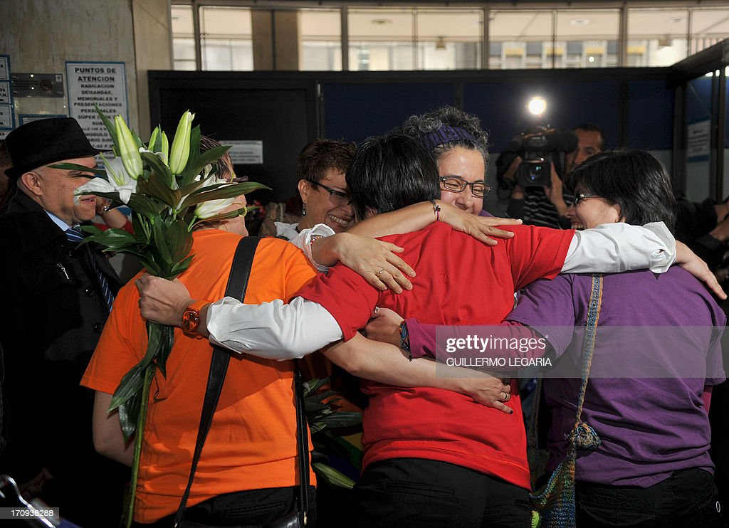 Gay couples embrace each other at the courthouse in Bogota, Colombia, on June 20, 2013, after filling documents to apply for registration of their marriages. From today Colombia will enter into a legal puzzle on gay marriage, as gay couples will go to notaries and judged without knowing if they will come out with the document as desired, given the legal vacuum that persists for such unions. AFP PHOTO/Guillermo LEGARIA