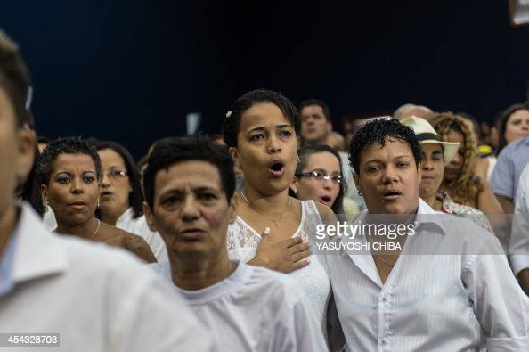 Gay couples sing the national anthem before their wedding ceremony at the Court of Justice of the State of Rio de Janeiro on December 8 2013 130 gay...
