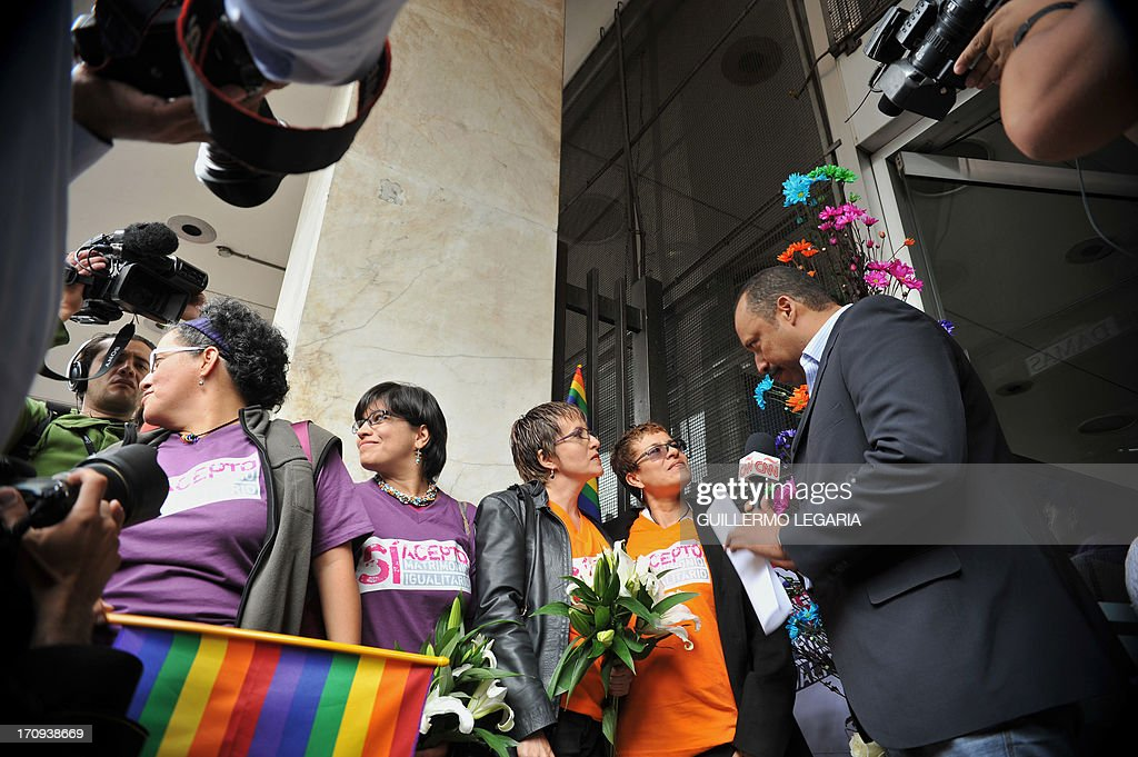 Gay couples speak with the press before filling documents at the court in Bogota, Colombia, on June 20, 2013, to apply for the registration of their marriage. From today Colombia will enter into a legal puzzle on gay marriage, as gay couples will go to notaries and judged without knowing if they will come out with the document as desired, given the legal vacuum that persists for such unions. AFP PHOTO/Guillermo LEGARIA