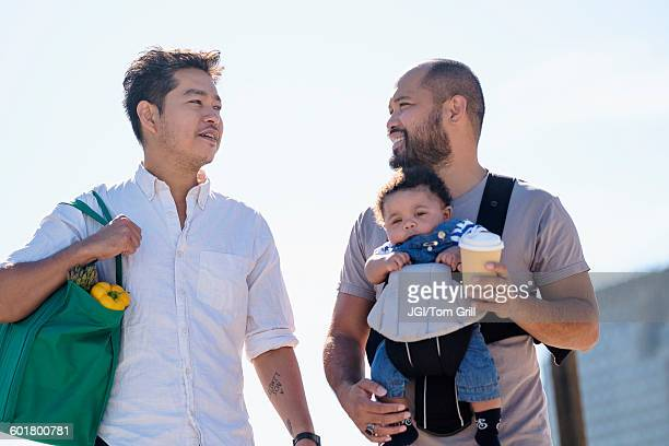 Gay fathers doing errands with baby son