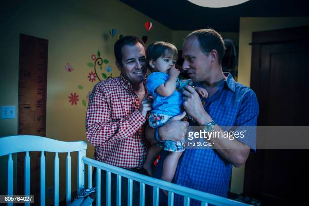 Gay fathers holding baby son in nursery