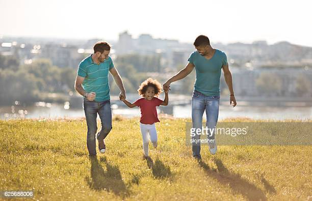 Gay parents running in the park with their adopted daughter.