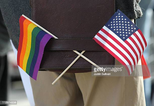 A gay pride and an American flag hang from a shoulder bag during a demonstration outside of the Phillip Burton Federal Building on June 13 2011 in...