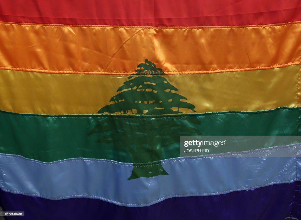 A gay pride flag bearing the cedar tree in the middle of it is carried by a human rights activists during an anti-homophobia rally in Beirut on April 30, 2013. Lebanese homosexuals, human rights activists and members from the NGO Helem (the Arabic acronym of 'Lebanese Protection for Lesbians, Gays, Bisexuals and Transgenders') rallied to condemn the arrest on the weekend of three gay men and one transgender civilian in the town of Dekwaneh east of Beirut at a nightclub who were allegedly verbally and sexually harassed at the municipality headquarters. AFP PHOTO/JOSEPH EID