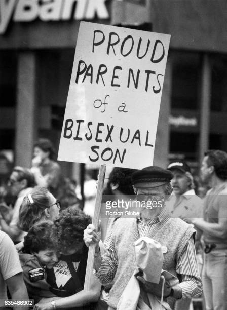Gay pride marchers make their way down Cambridge Street in Boston during a parade on Lesbian and Gay Pride Day June 9 1990 A man holds up a sign that...