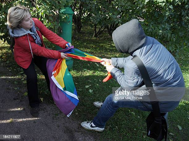 A gay rights activist fights for her rainbow flag against an antigay protester during a gay pride event in Saint Petersburg on October 12 2013...
