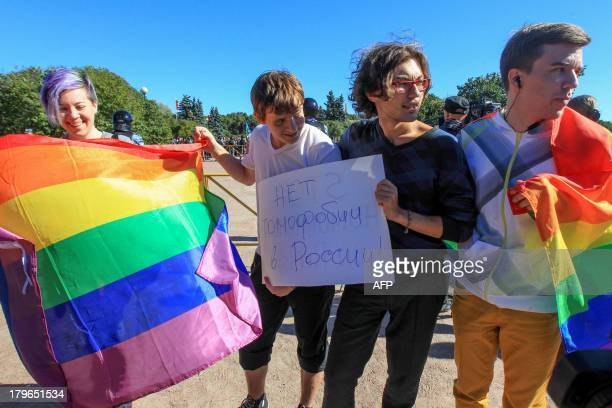 Gay rights activist holds rainbow flags and posters as they take part in a gay pride event in Saint Petersburg on September 6 2013 The poster reads...